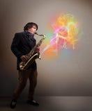 使用在有五颜六色的摘要的萨克斯管的可爱的音乐家 库存照片