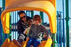 使用在有他们的母亲的公园的愉快的孩子 库存图片