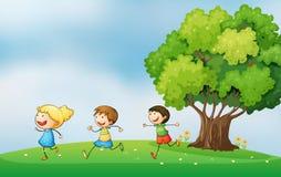 使用在有大树的小山顶的精力充沛的孩子 库存图片