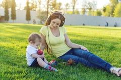 使用在有她的可爱宝贝儿子的一个绿色草甸的年轻现代妈妈在一个晴朗的公园 母性喜悦的概念  免版税库存照片