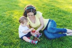 使用在有她的可爱宝贝儿子的一个绿色草甸的美丽的现代妈妈在一个晴朗的公园 母性喜悦的概念  库存照片