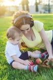 使用在有她的可爱宝贝儿子的一个绿色草甸的美丽的现代妈妈在一个晴朗的公园 母性喜悦的概念  免版税库存照片