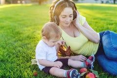 使用在有她的可爱宝贝儿子的一个绿色草甸的美丽的现代妈妈在一个晴朗的公园 母性喜悦的概念  库存图片
