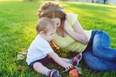 使用在有她的可爱宝贝儿子的一个绿色草甸的美丽的现代妈妈在一个晴朗的公园 母性喜悦的概念  免版税库存图片