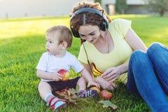 使用在有她的可爱宝贝儿子的一个绿色草甸的耳机的年轻现代妈妈在一个晴朗的公园 母性喜悦 免版税库存照片