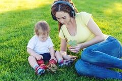 使用在有她的可爱宝贝儿子的一个绿色草甸的耳机的年轻现代妈妈在一个晴朗的公园 母性喜悦 图库摄影
