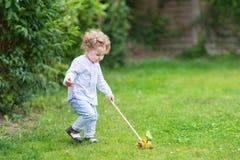 使用在有木玩具的庭院里的卷曲女婴 图库摄影