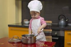 使用在有杓子和平底深锅的厨房里的厨师衣服的小逗人喜爱的女孩 免版税库存照片