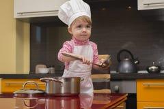 使用在有杓子和平底深锅的厨房里的厨师衣服的小逗人喜爱的女孩 免版税库存图片