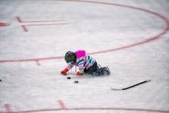 使用在有顽童的曲棍球溜冰场的盔甲的小女孩 免版税库存照片