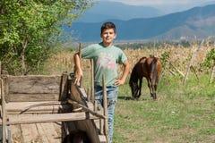 使用在有马的有机阿拉扎尼河谷的农场和葡萄园的未认出的愉快的孩子与山 库存图片