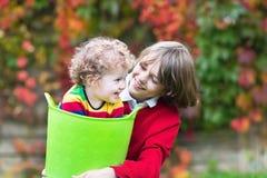 使用在有洗衣篮的庭院里的两个孩子 库存照片