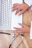 使用在木书桌上的医生膝上型计算机 免版税库存图片