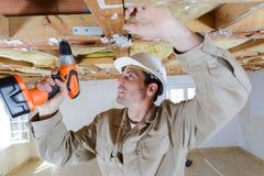 使用在木天花板安装托梁的建造者无绳的螺丝刀 库存照片