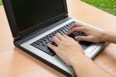 使用在木桌上的人膝上型计算机 免版税库存照片