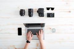 使用在木桌上的年轻人的手膝上型计算机 图库摄影