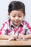 使用在木桌上的画象逗人喜爱的亚裔女孩 免版税库存照片
