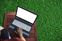 使用在木椅子的一个人计算机膝上型计算机与草地板 裁减路线屏幕 图库摄影