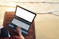 使用在木sunbath躺椅的一个人计算机膝上型计算机在海滩在夏天在日落 裁减路线计算机笔记本scree 免版税库存照片