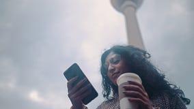 使用在柏林的背景的美丽的混合的族种妇女聪明的电话技术app居住的都市愉快的生活方式 股票视频