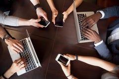 使用在桌, t上的不同的多种族人民膝上型计算机智能手机 免版税库存照片