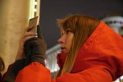 使用在欧洲圣诞节市场上的妇女智能手机 免版税库存照片