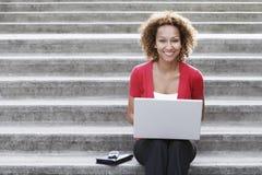 使用在步的妇女膝上型计算机户外 免版税库存图片