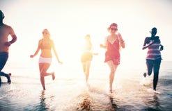 使用在水中的朋友在海滩 免版税库存图片
