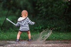 使用在水坑的小男孩在夏天节日,波多利斯克7月2017年,俄罗斯音乐的春天森林里  免版税库存照片