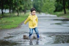 使用在水坑的小男孩 免版税库存照片