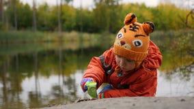 使用在池塘的岸的孩子 在新鲜空气的步行 秋天横向 天空和树的反射 库存照片