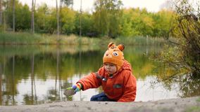使用在池塘的岸的孩子 在新鲜空气的步行 秋天横向 天空和树的反射 免版税库存照片
