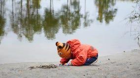 使用在池塘的岸的孩子 在新鲜空气的步行 秋天横向 天空和树的反射 股票视频