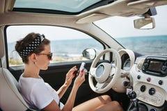 使用在汽车的少妇旅客电话 免版税库存照片