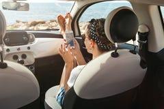 使用在汽车的少妇旅客电话 免版税图库摄影