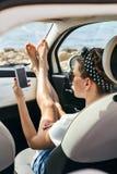 使用在汽车的少妇旅客电话 库存照片