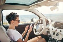 使用在汽车的少妇旅客电话 免版税库存图片
