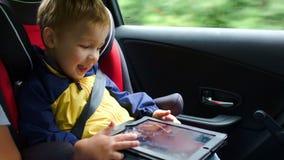 使用在汽车的片剂计算机上的小男孩 影视素材