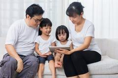 使用在沙发的亚裔中国父母和女儿片剂 免版税图库摄影