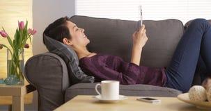 使用在沙发的亚裔妇女片剂 免版税库存图片