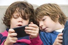 使用在沙发的兄弟和姐妹巧妙的电话 免版税库存照片