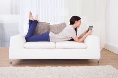 使用在沙发的妇女数字式片剂 库存图片