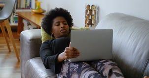 使用在沙发的妇女膝上型计算机在一个舒适的家4k 股票视频