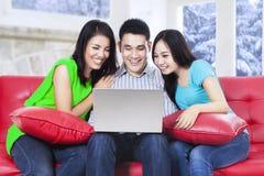 使用在沙发的小组亚裔人民膝上型计算机 免版税图库摄影