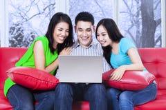 使用在沙发的小组朋友膝上型计算机 免版税库存照片