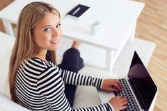 使用在沙发的微笑的妇女背面图膝上型计算机 免版税库存照片