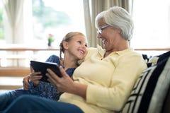 使用在沙发的微笑的孙女和祖母数字式片剂 免版税库存图片