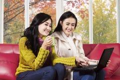 使用在沙发的快乐的妇女膝上型计算机 库存照片