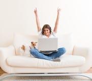 使用在沙发的快乐的妇女膝上型计算机 免版税库存图片