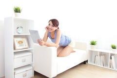 使用在沙发的愉快的妇女片剂个人计算机 免版税库存照片
